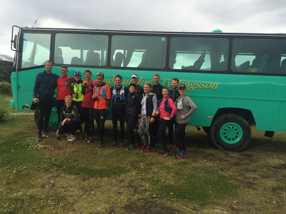 A running group in front of a bus