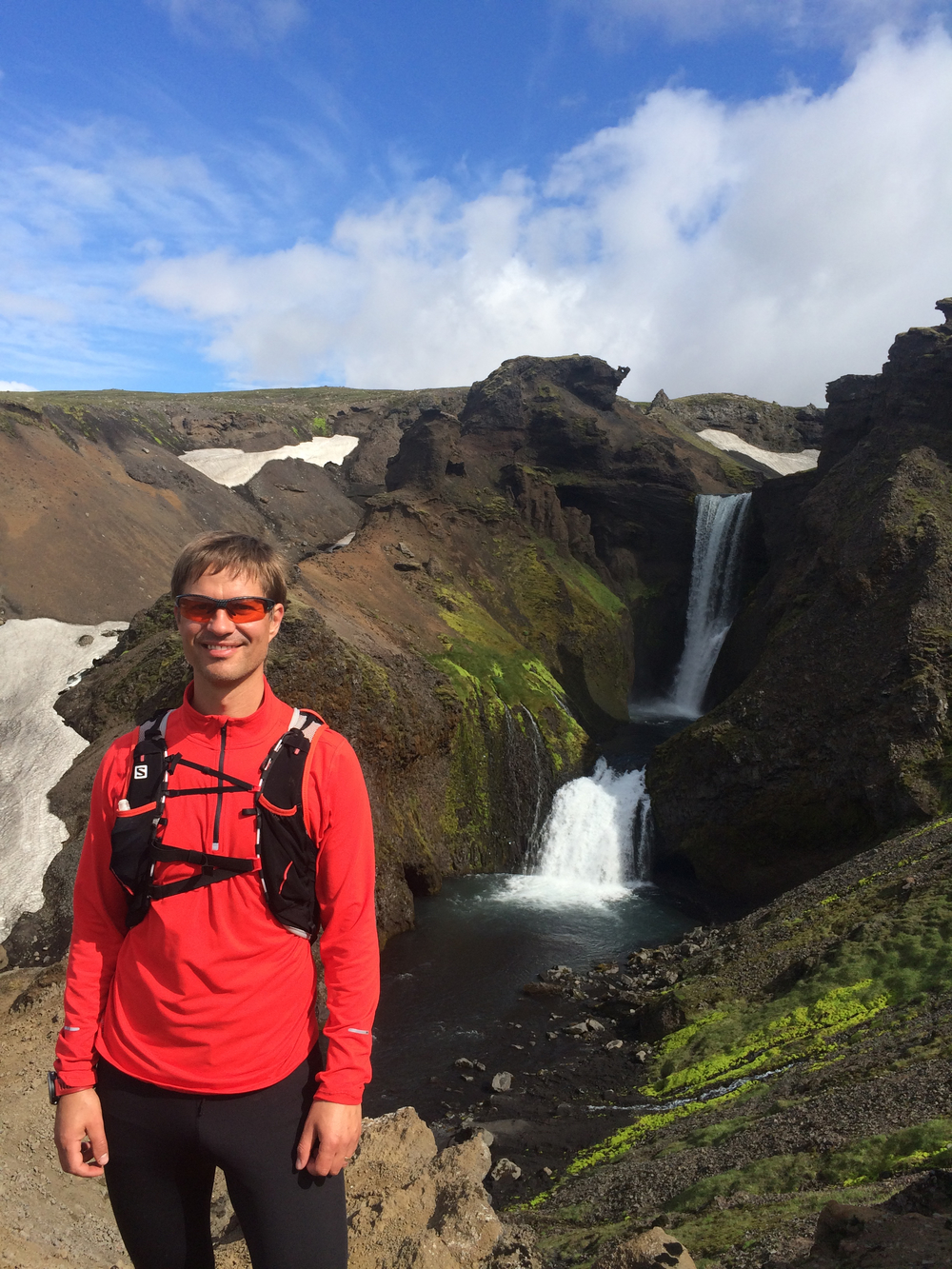 Standing in red, smiling, in front of waterfalls