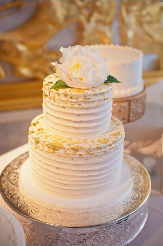 two tier white wedding cake with gold flake