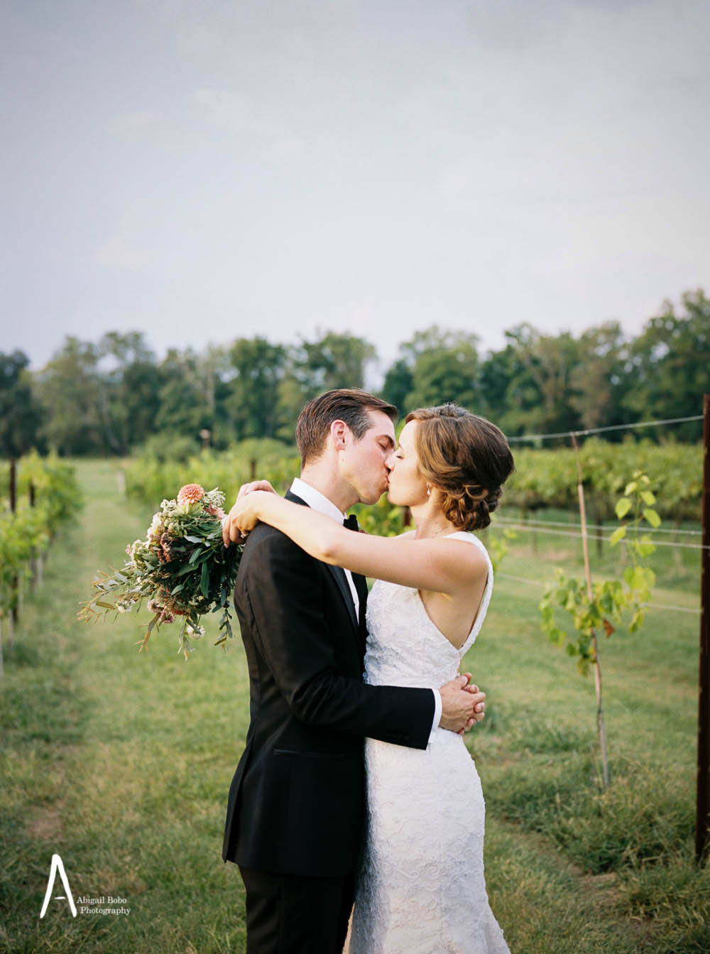 bride and groom kissing in a vineyard
