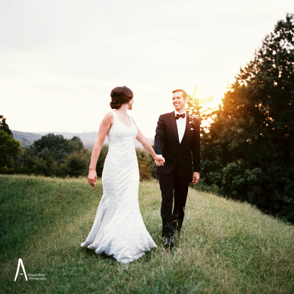 bride and groom walking through a field hand in hand