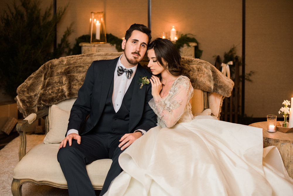 bride groom sitting on couch-fur-fireplace.jpg