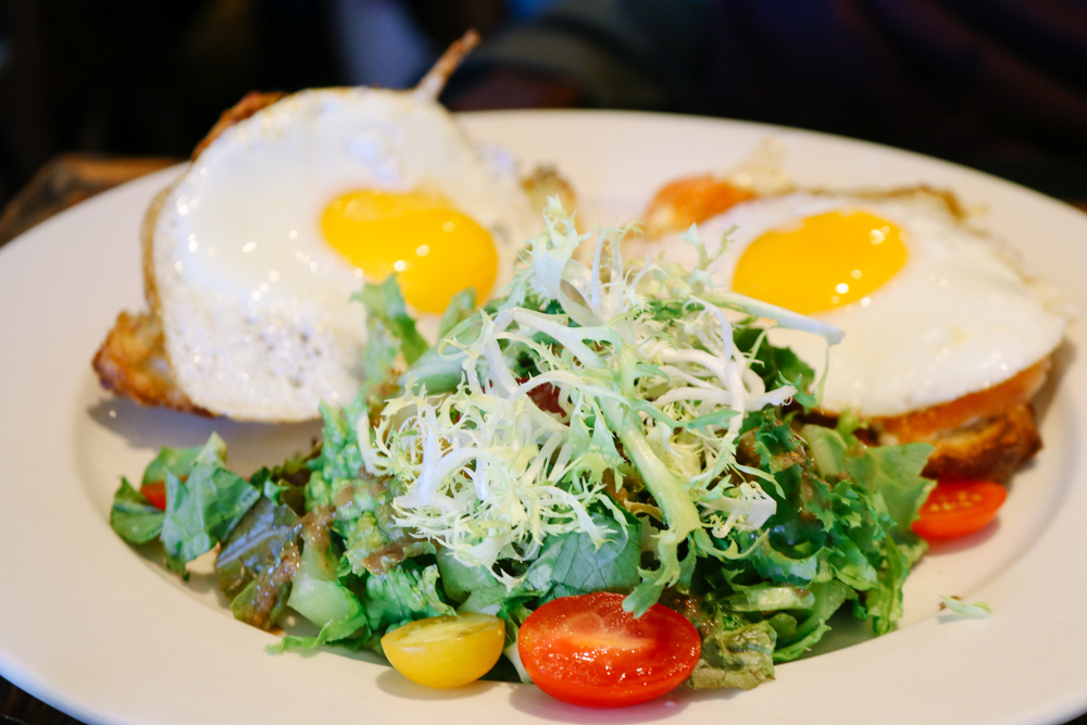 Croissant Oeufs Fromage,  2 Sunny Side eggs, avocado spread, melted mozzarella & gravlax on croissant. Served with mixed greens