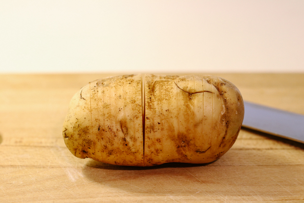 Using a sharp knife, make crosswise cuts in each potato, about 1/8 inch apart, stopping about 1/4 inch from the bottom.