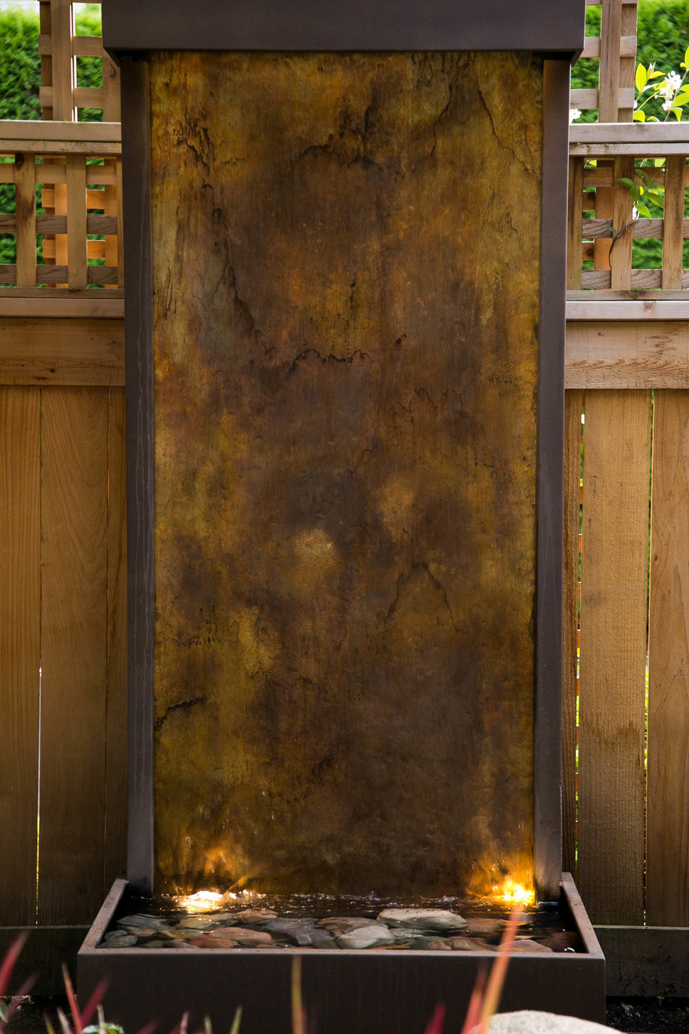 Vertical water feature with a hammered brass panel and custom patina.  Up and down lighting added for a spectacular focal point in the evenings.