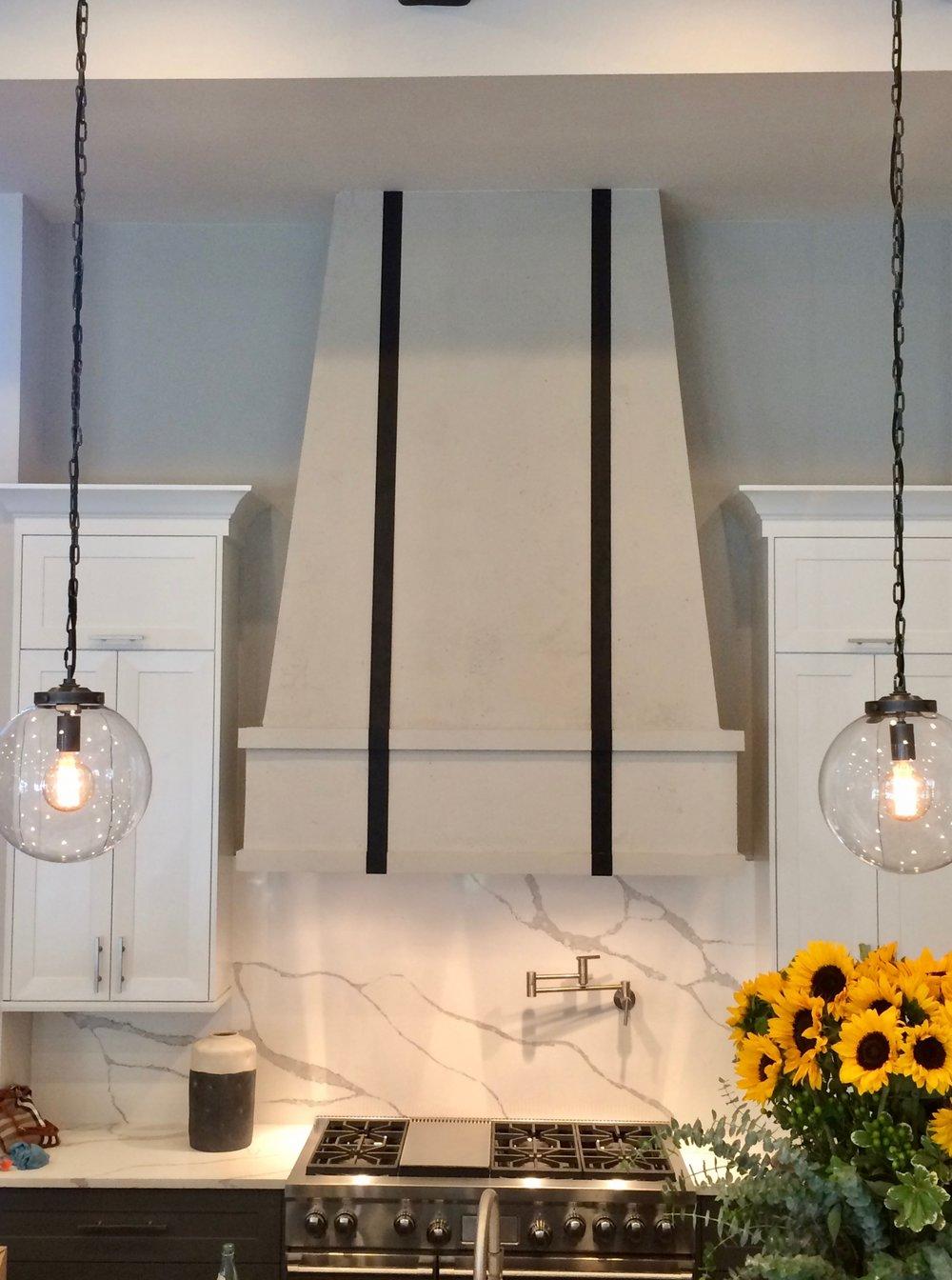 Limestone Hood Vent with Custom Metal Straps. Dimensions: 7.5'H x 5'W