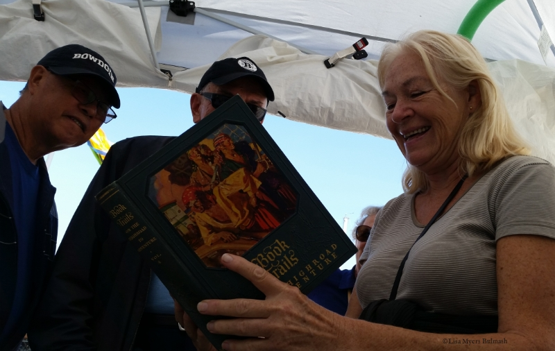 Visitors to my Fresh Paint festival booth examine a book I altered before their eyes.