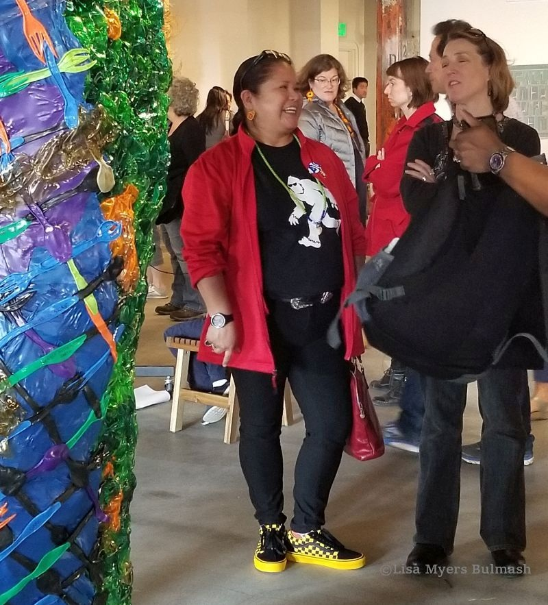 """HollyAnna DeCoteau Littlebull (in red jacket) with an admirer of her work at  """"Together we lift the sky"""""""
