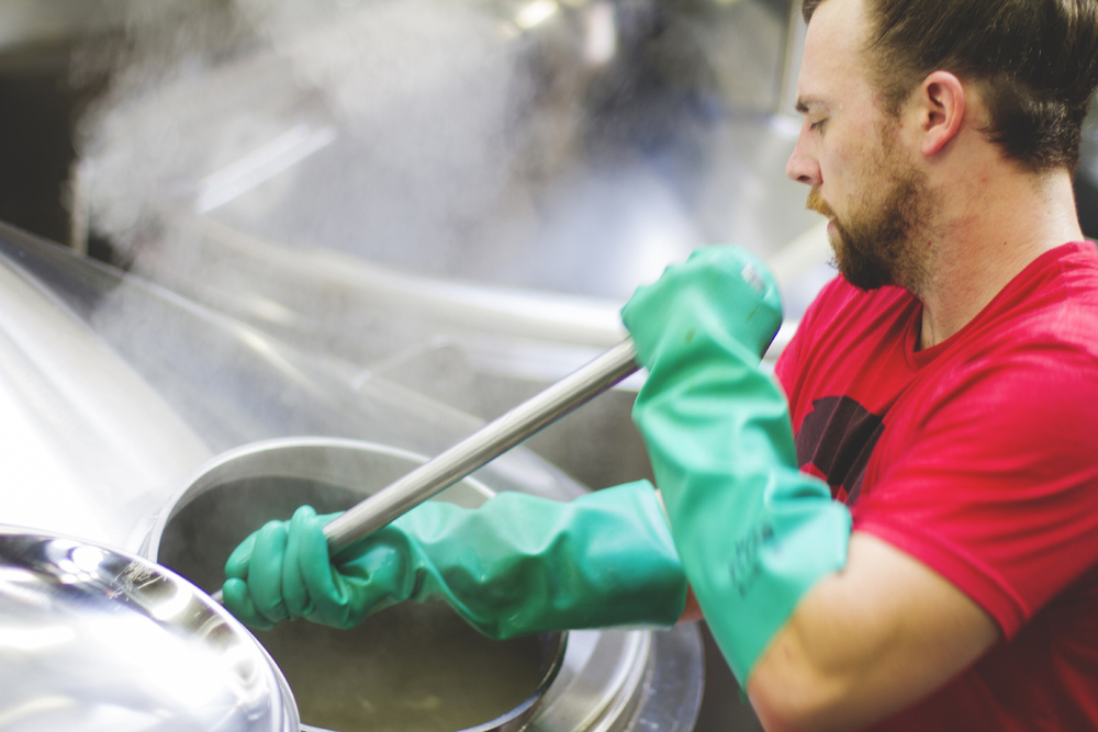 Brewmaster Frank Trosset mixing hops into the boil.