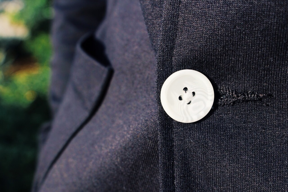 Details count. These white buttons pop with stark contrast against this H&M black blazer.