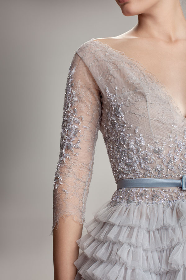 The gorgeous intricate beading and embroidery on this gown's lace sleeves and bodice add to its ethereal feel.
