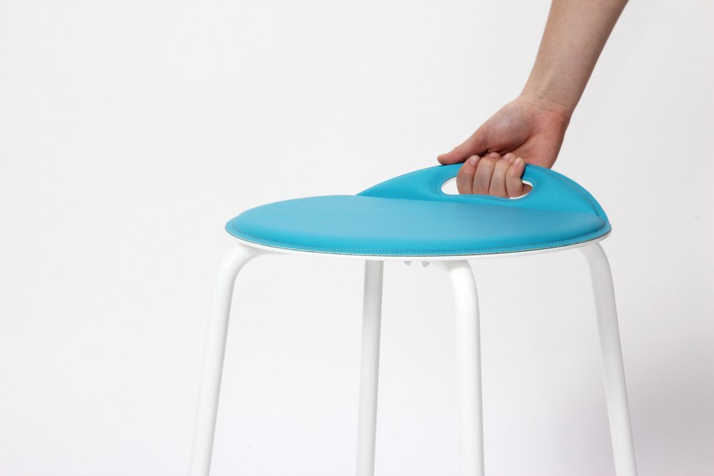 The cut-out handle allows the stool to be lifted and moved with one hand (shown with magnetic seat cover).