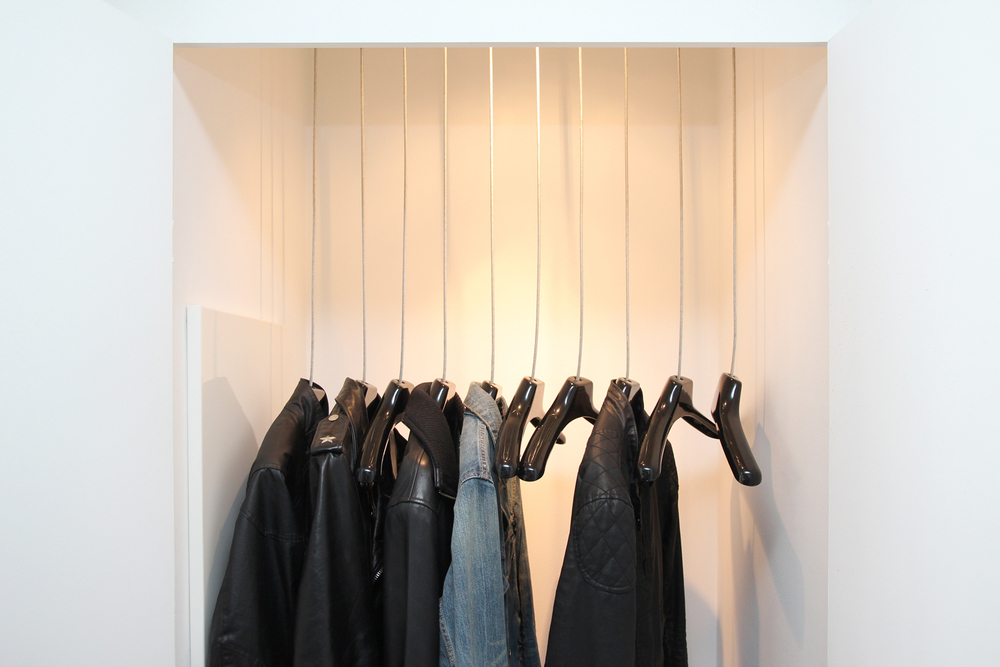The entry closet reveals suspended coat hangers made from aircraft cable.