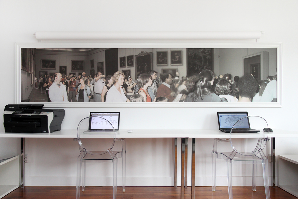 A 12' panorama taken of the familiar crowds gathered to see the Mona Lisa (which can be seen on the right) hangs above two workstations.