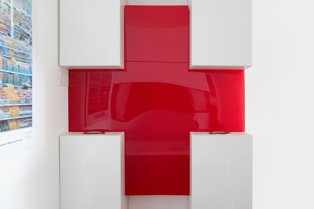 An acrylic red cross marks the center of four unassuming cabinets...