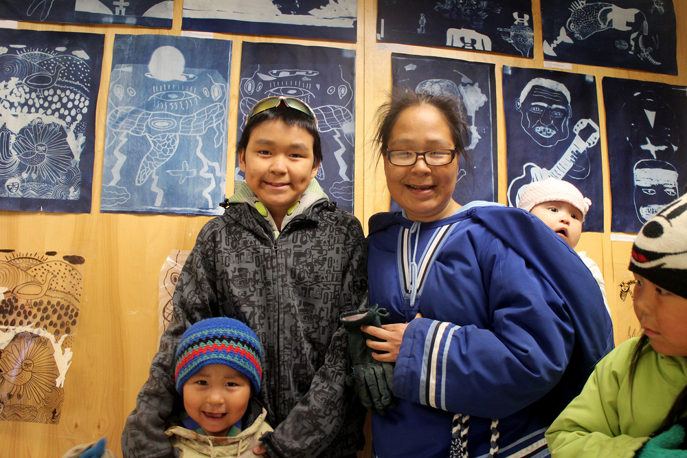 Tommy Quvianaqtuliaq and his family in front of his cyanotype prints (lightning and eyes!)