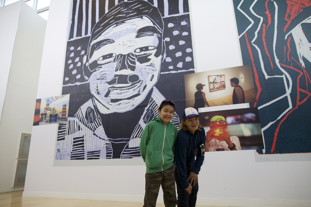 Tommy Quvianaqtuliaq, left, Parr Josephee, right. Tommy's self-portrait is the giant linocut image behind him, and Parr stands beside one of many photos of himself as part of the Piliriqatigiingniq mural project in Toronto, 2015.