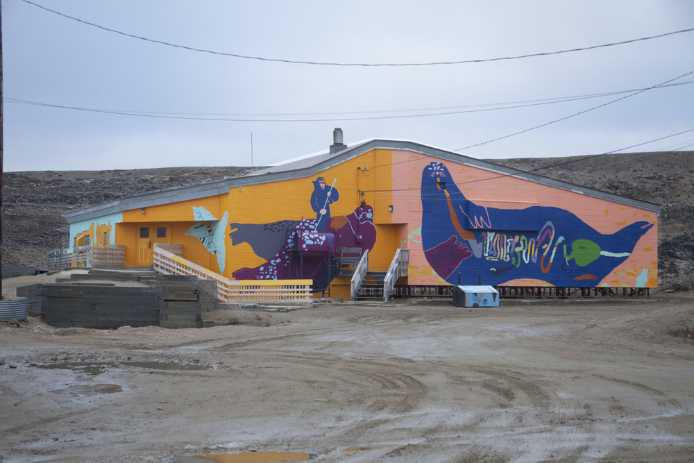 Front of the Community Hall. Left to right drawings by Ezeevalu Samayualie, Harry Josephee, Christine Adamie. Kevin Qimirpik, Tommy Quvianaqtuliaq, and Salomonie Ashoona.