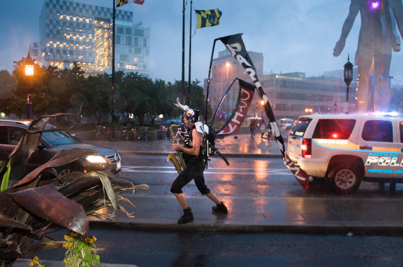 "Aran Keating following his impulses during 2013 Artscape in the pouring rain. Playing saxophone with enormous ""Party Hard"" and ""Drink Beer"" banners in tow. Photo Credit: Chuck Patch (Flickr)"