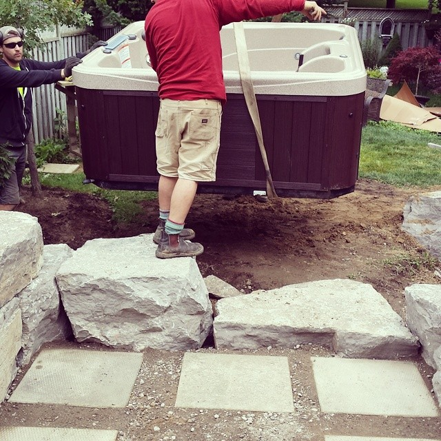 The guys lifting in a hot - tub into a pretty precarious spot. #hottub #armourstone #stonework #hardscaping
