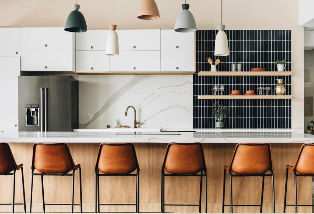 This kitchen by Studio125 created a focal point with this black  Fireclay Tile , the black color blocking is what pulls the whole space together and the verticle application helps change draw your eye to it as everything else in the kitchen is very linear.
