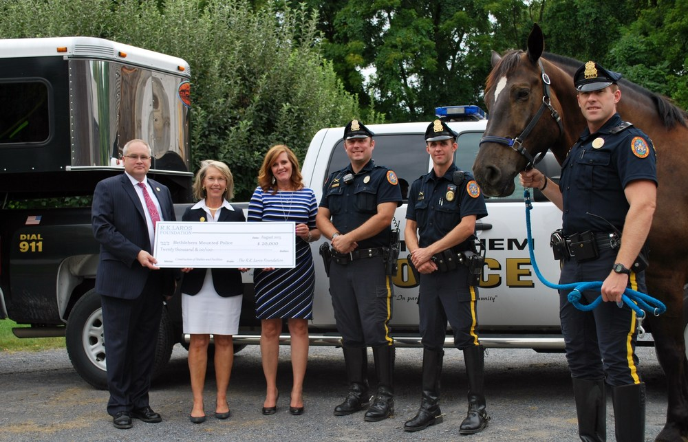 Laros Trustee Laurie Gostley Hackett and Executive Director Sharon Zondag presenting the R.K. Laros grant to the Bethlehem Mounted Police.