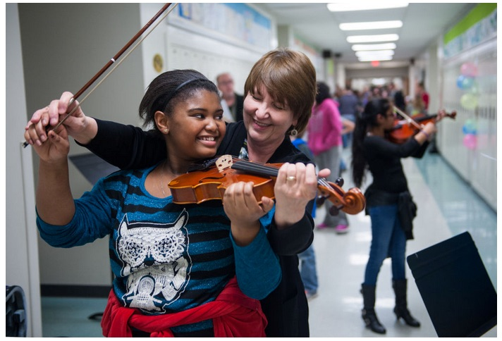 CPS orchestra teacher Margaret Lawless assists West Boulevard Elementary student Malaya Givens, 11, in playing the viola Thursday while Keya Patel, 10, plays in the background at a band and orchestra enrollment night at Gentry Middle School. It was Malaya's first time playing an instrument.
