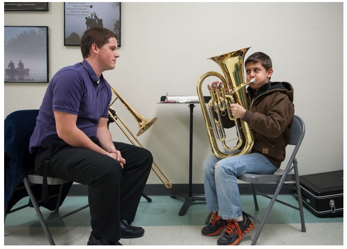 Keller Shelton, left, assists Daniel Benedetti, 10, in playing the baritone at one of the Columbia Public Schools' sixth grade band and orchestra enrollment nights Thursday at Gentry Middle School. This was Daniel's first time playing an instrument.