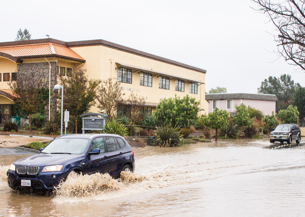 STAR // Gustavo Vasquez Car driving through high flood zone on Avram Avenue in front of Rohnert Park City Hall today.