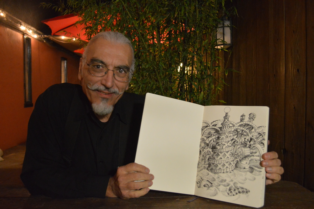 STAR// Michellle Welling   Musician and artist Robert Dougherty sharing one of his sketches. Dougherty was one of the many local artists whose work was exhibited at Redwood Cafe on Feb. 10.