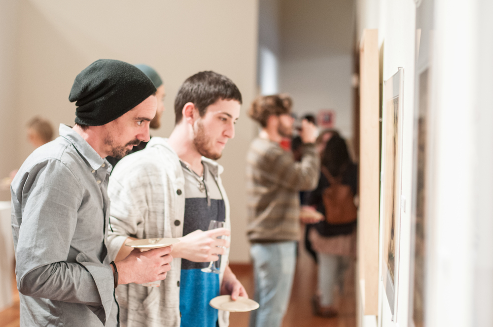 STAR // Gustavo Vasquez Andrew Scanlon, art studio sculpture major and Vinnie Schraner, art studio painting major, examining artwork showcased at the Faculty Art Show on Thursday during the University Art Gallery reception.
