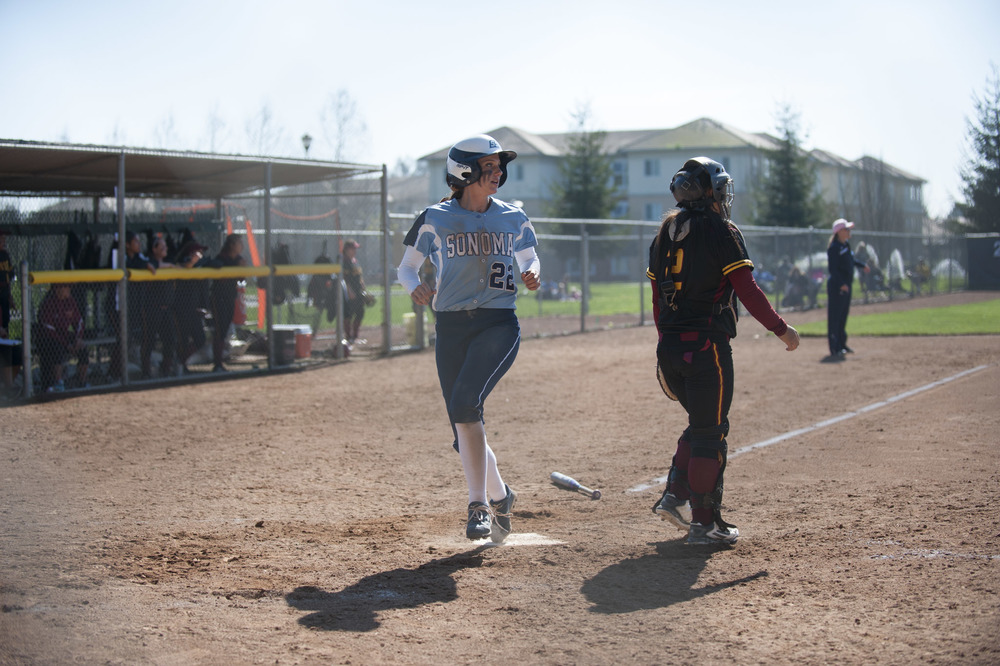 STAR // Connor Gibson   Senior Holli Brown crosses the plate. Junior Amanda Llerena (8) and senior Amanda Rosetta (16) keep it light on the field.
