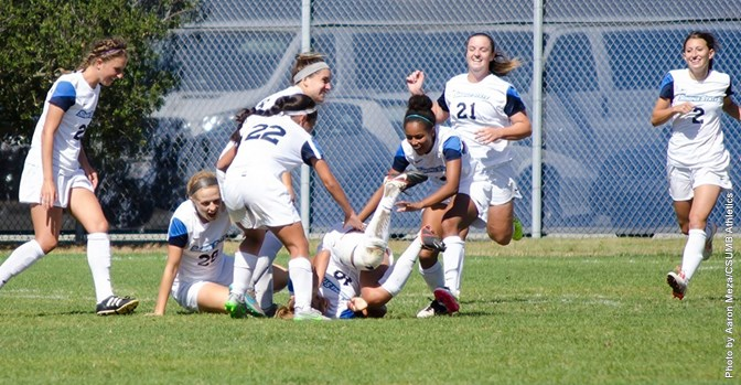 Junior Kristal Luna is rushed by teammates after scoring the game-winning goal against CSUMB.