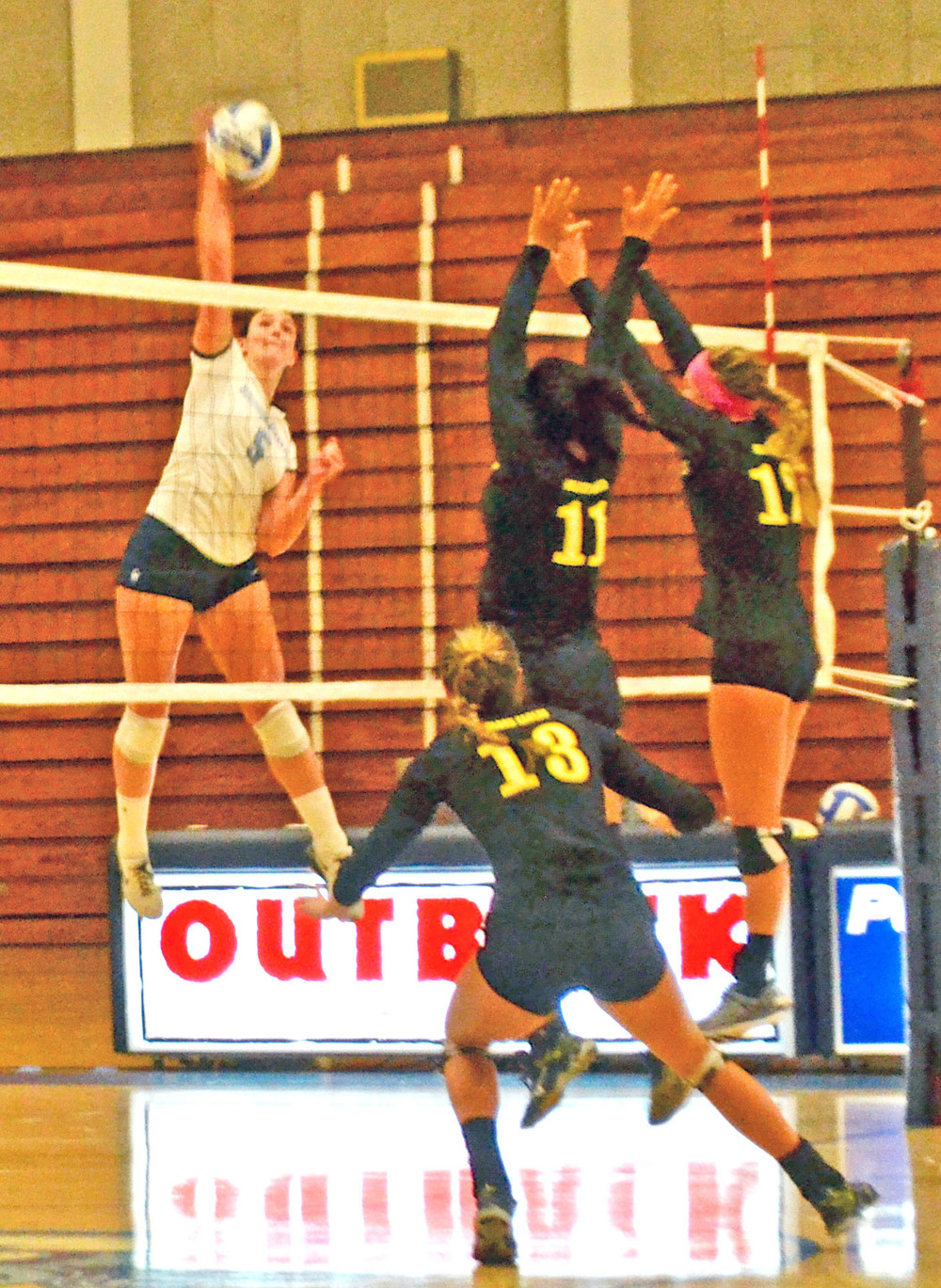 Senior Caylie Seitz goes for the kill in between three defenders.