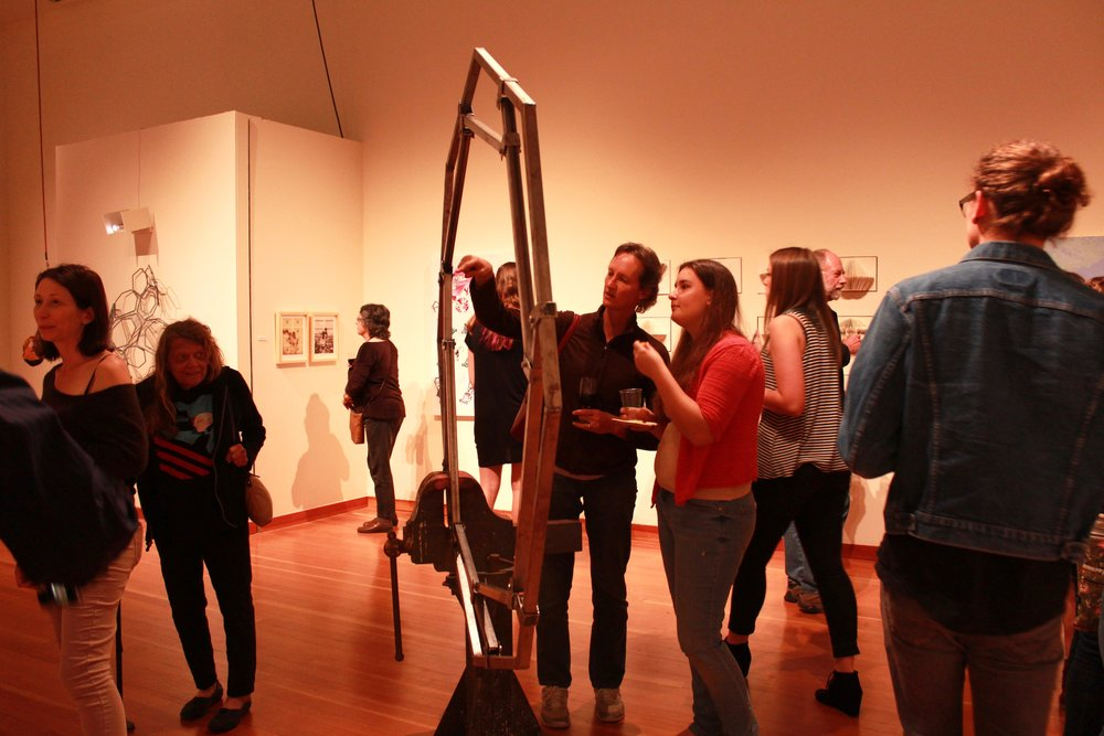 STAR // Sara Wildman  Students discuss art pieces on display at the 2016 BFA Show.
