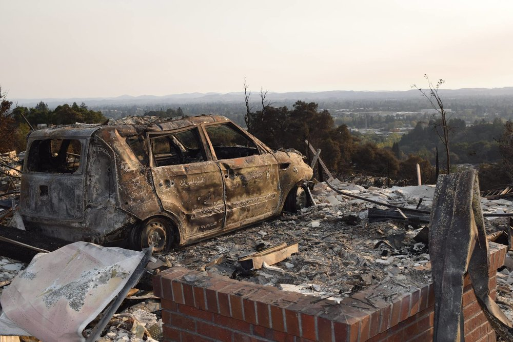 STAR // Paul Gullixson  A destroyed car looks out over Santa Rosa to the west on Alturia Drive near The Boulders at Fountaingrove, where hundreds of homes were lost in the Oct. 9 firestorm.