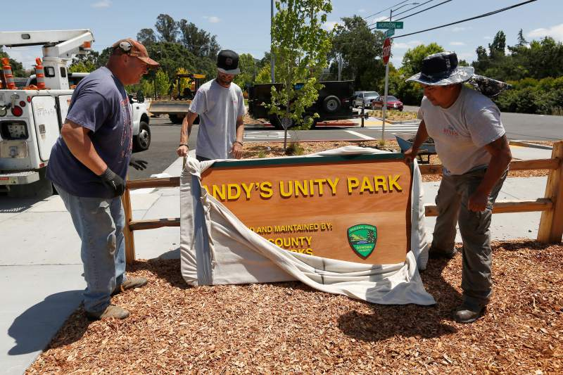 Dave Bailey, left, of Healdsburg Signs, with Thomas Rogers and Miguel Reyes of Reyes Sign Erection unwrap the official Sonoma County Parks sign for Andy's Unity Park in Santa Rosa on May 31, 2018.