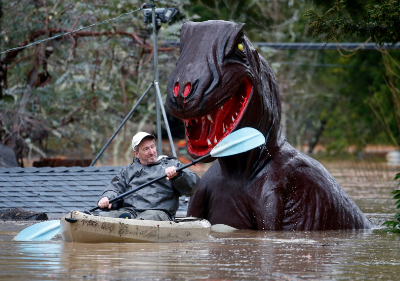 Rich Wilson, seen above, is seen paddling through floodwaters that severely damaged a local miniature golf course in Guerneville last month.