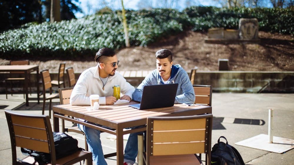 STAR // Gabriella Novello   Students Brenden Gallardo and Tyee Stokman work together on the outside patio of Charlie Brown's in McCabe Plaza.