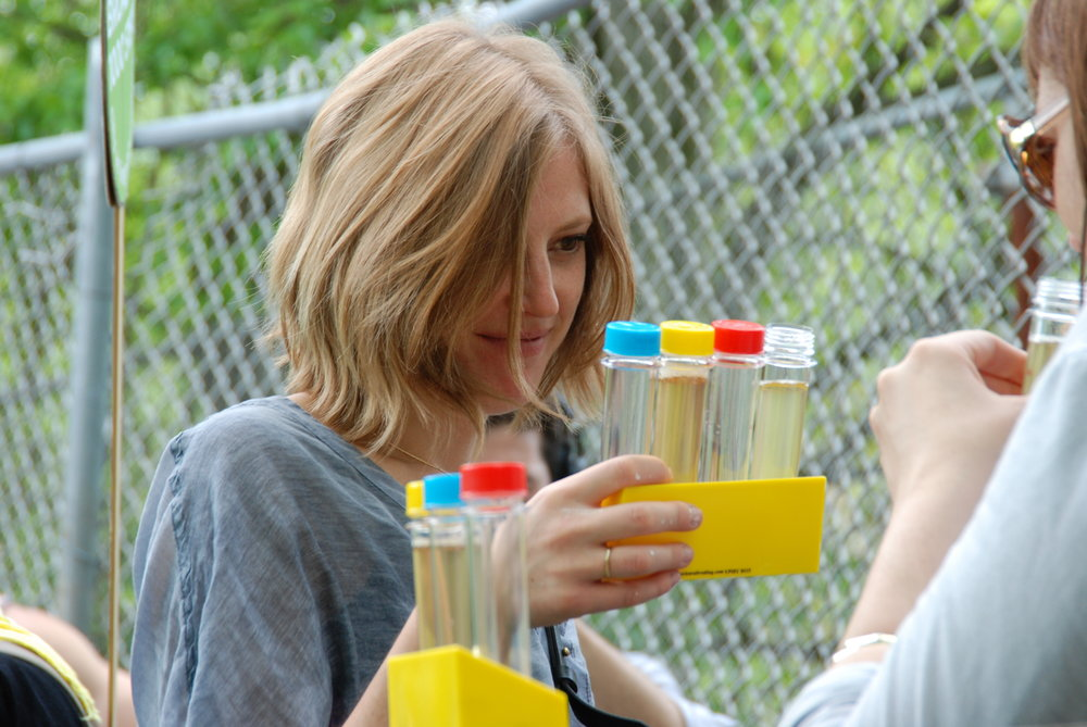 An attendee of a CALL WALK in Spring 2015 examines water samples. These interactive experiences will be facilitated in cities across the country through the CALL/FRAMEWORK
