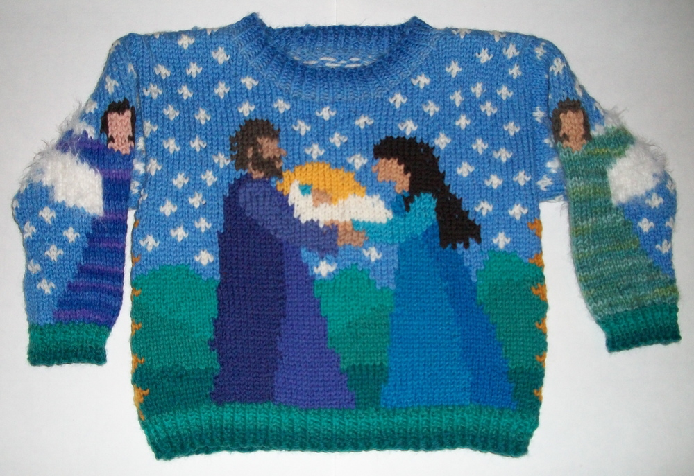 ONE YEAR: CHRISTMAS FRONT    On the front are Mary, Joseph, and Jesus. On the back is a shepherd and a sheep under a bright star in the starry sky. The sleeves have angels. The neck ribbing is shades of blue. The wrists and hem ribbing is shades of green.