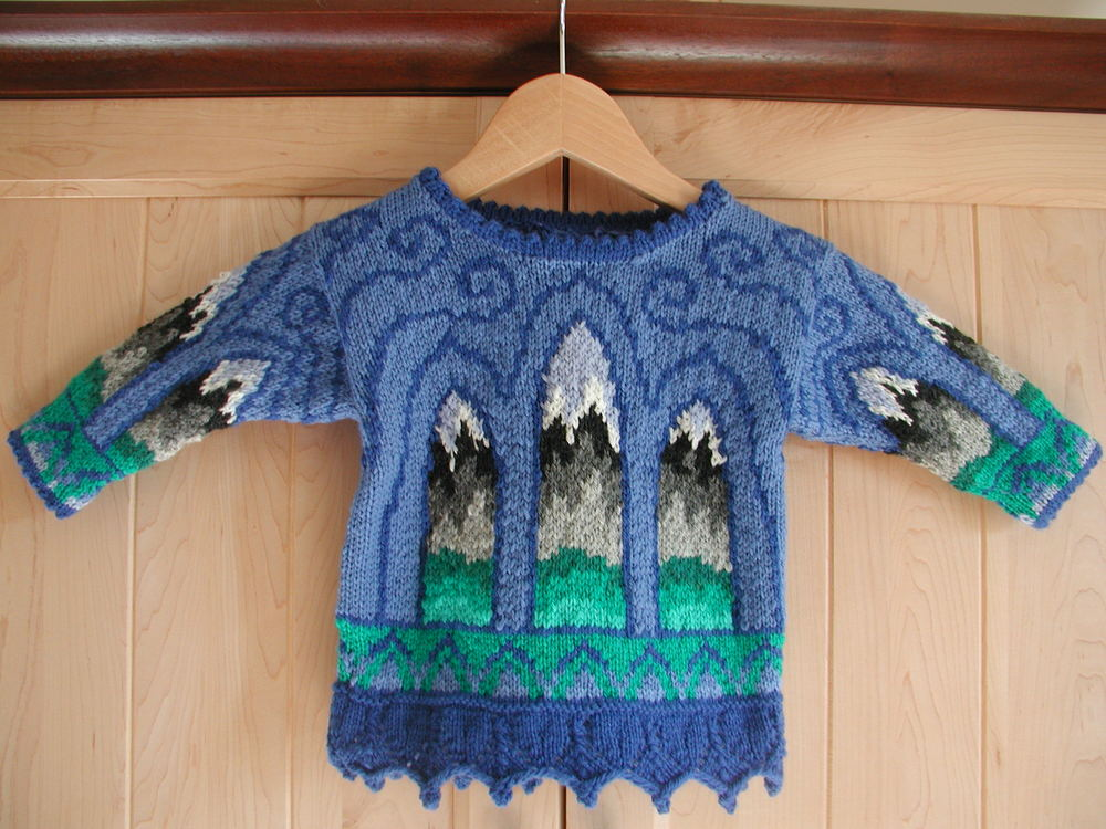 ONE YEAR: CHURCH WINDOWS    I only have one picture of this sweater, but the front and back are identical. The gothic windows show shades of green and mountains in grey. The foreground is periwinkle swirls on lighter blue. The wrists and hem trim is arches in blues on green. There is a lace pattern at the hem. The neck and wrists trim is picot trim in periwinkle.