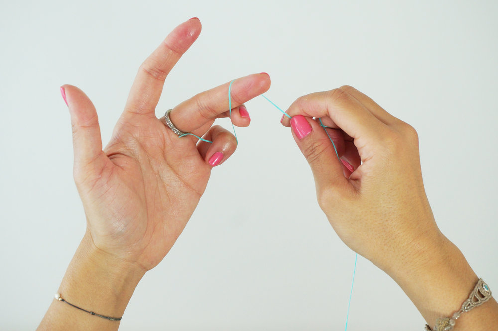 2.  TWIRL 1-2x around your middle finger on one hand.