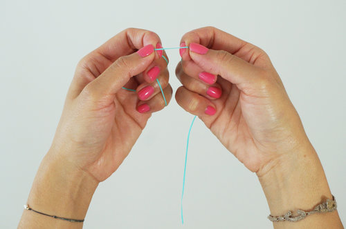 4. Hold floss with your pointers and thumbs close together, no more than 1 inch apart.