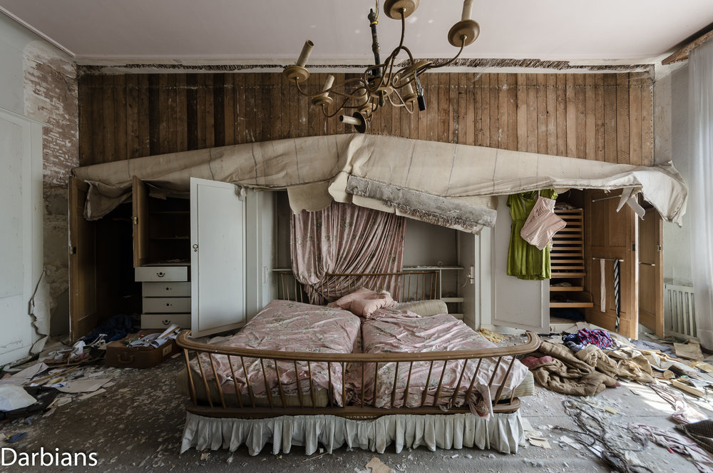 The large bed set in the built in wardrobe which is holding up the wallpaper.