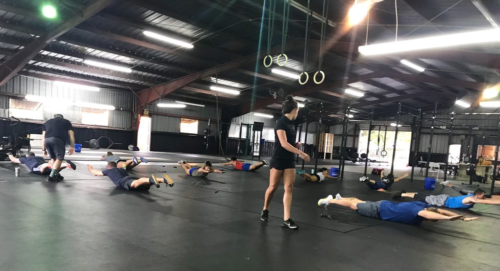 Nikolle and Joel actively coaching during a session of Tabata Hollow & Arch Holds