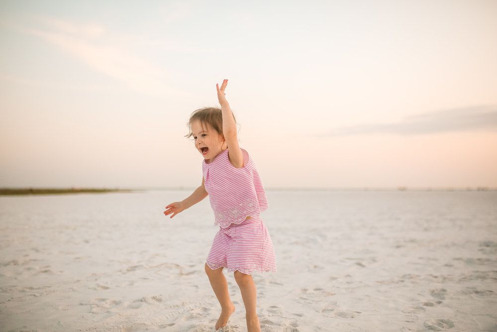 little girl jumping on beach