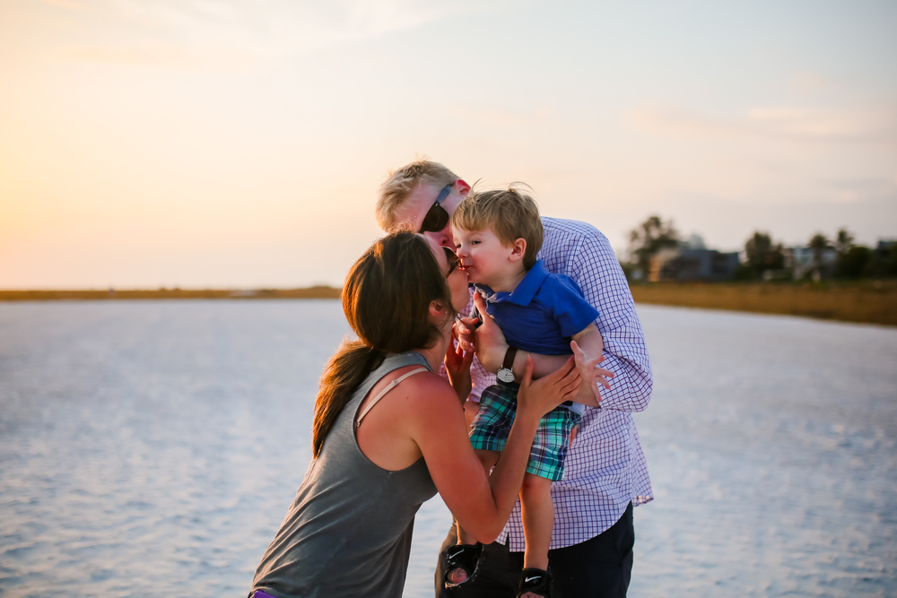 family sunset kiss with little boy