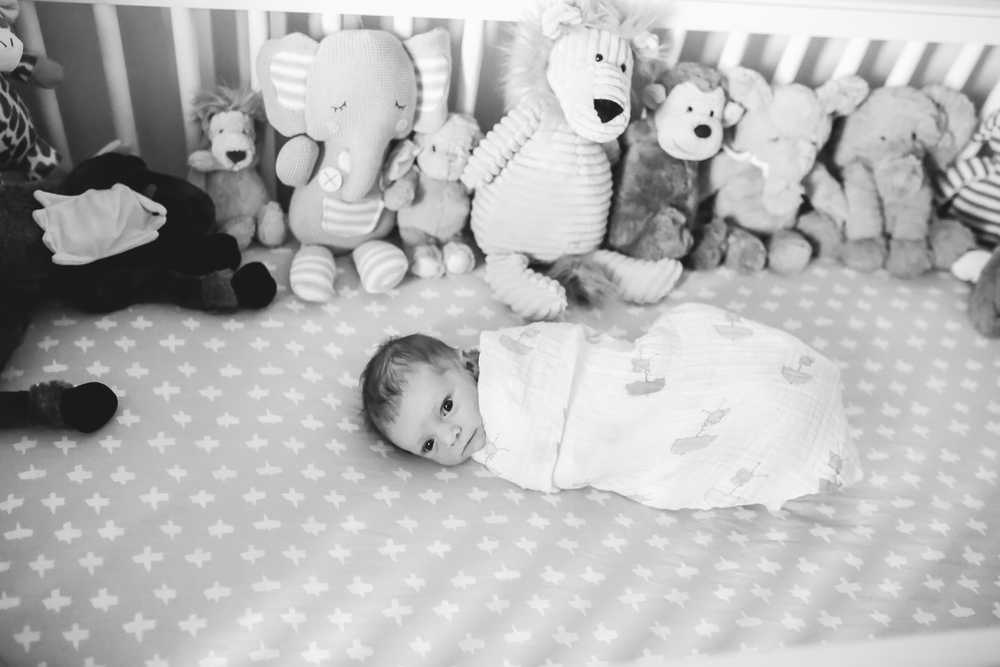 baby in crib with stuffed animals