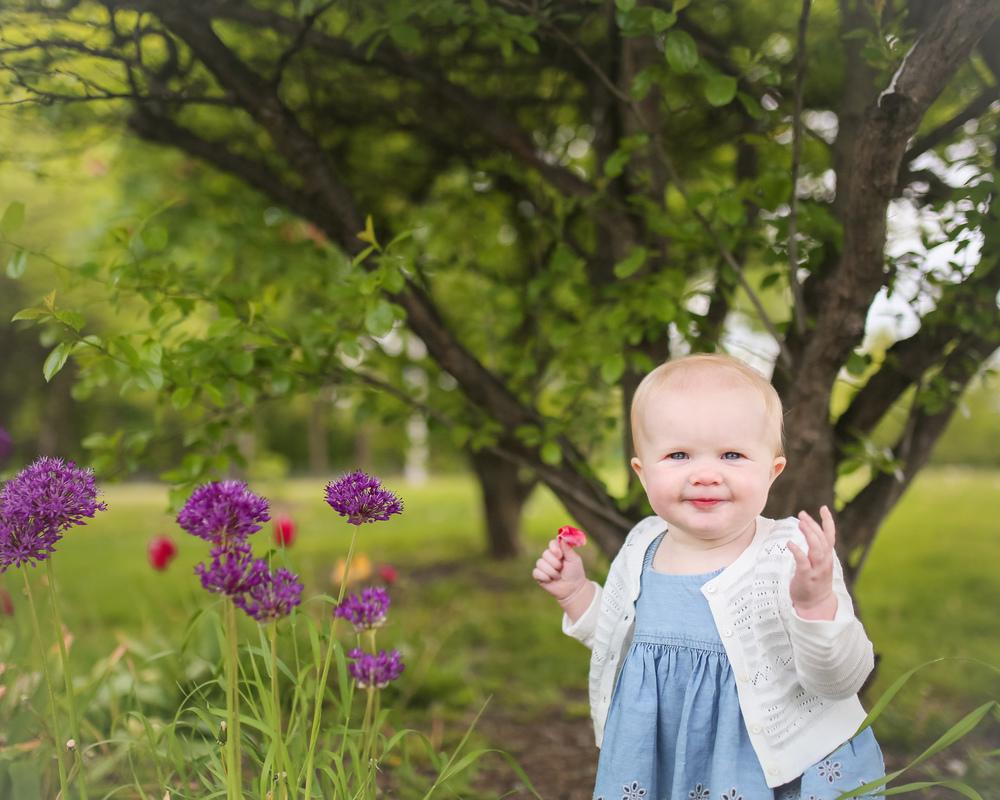 baby girl holding flower petal